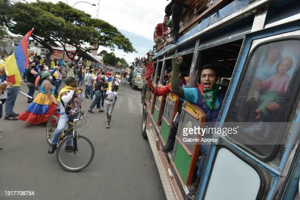 Member of the Indigenous Minga waves as they pass by Puerto Resistencia sector where their residents cheer and thank them for his presence in the...