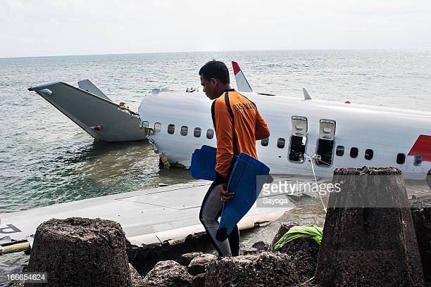 A member of the Indonesia Search and Rescue Agency prepares to search the CVR inside the wreckage of the Lion Air plane on April 15 2013 in Badung...