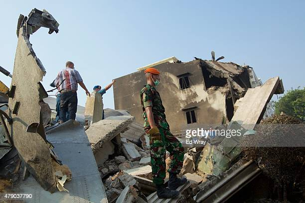 A member of the Indonesian military looks over the wreckage of a military transport plane which crashed into a building on June 30 2015 in Medan...
