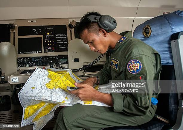 A member of the Indonesian military reads a map during a search and rescue operation for missing Malaysian air carrier AirAsia flight QZ8501 over the...