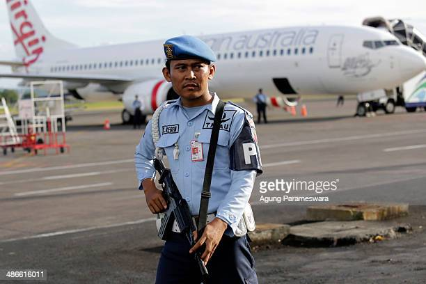 A member of the Indonesian military stands guard near a Virgin Australia airplane which was forced to land at International Ngurah Rai Airport after...