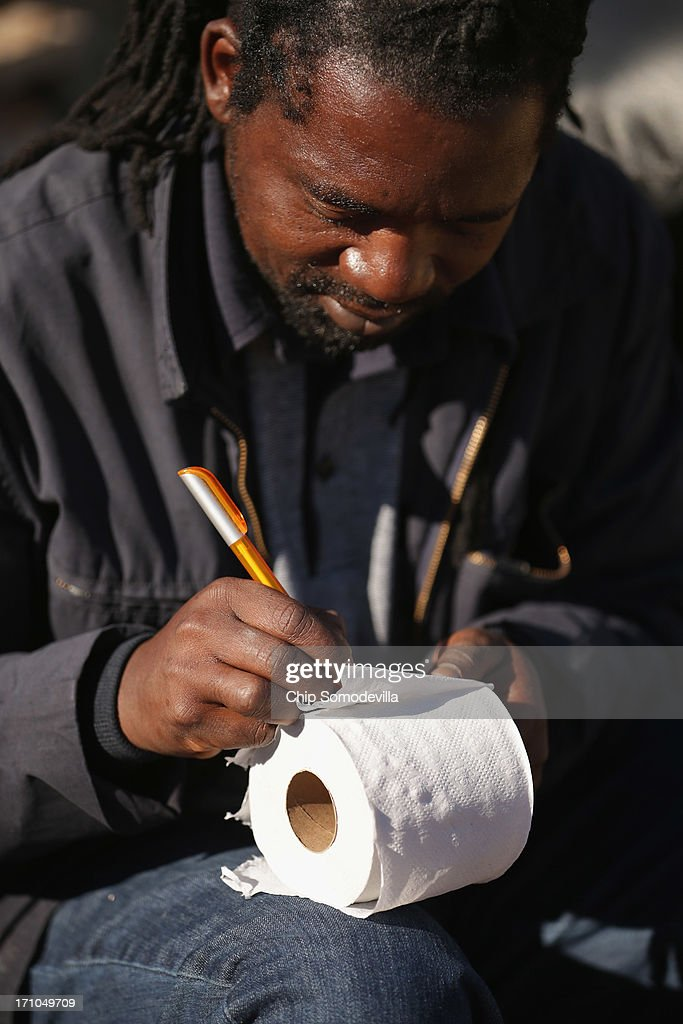 A member of the Indumiso Yamakholwa In Zion church writes prayers on toilet paper before stuffing them into a bottle ahead of a prayer service in the Yeoville neighborhood June 21, 2013 in Johannesburg, South Africa. After being prayed over and blessed, worshipers will smash the bottles to release the prayers to God. The worn, arid space on top of the Yeoville hill offers worshipers of various Christian denominations from South African, Botswana, Zimbabwe, the Democratic Republic of Congo and other African nations an open-air space where they can publicly practice their faith with a scenic view of downtown Johannesburg.