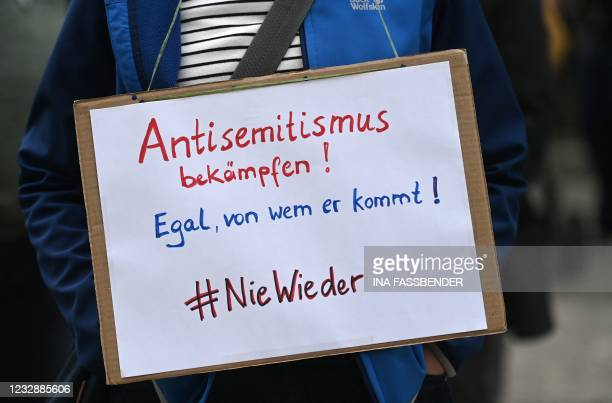 Member of the Initiative against Anti-Semitism Gelsenkirchen holds a placard reading 'fight antisemitism - No matter where it comes from - #never...