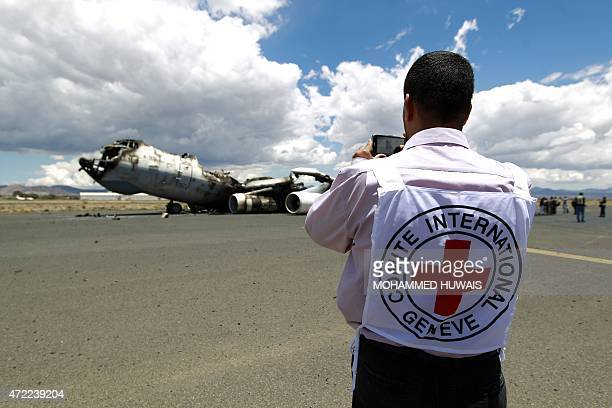 A member of the International Committee of the Red Cross takes pictures of the wreckage of a Yemeni air force military transport aircraft on the...