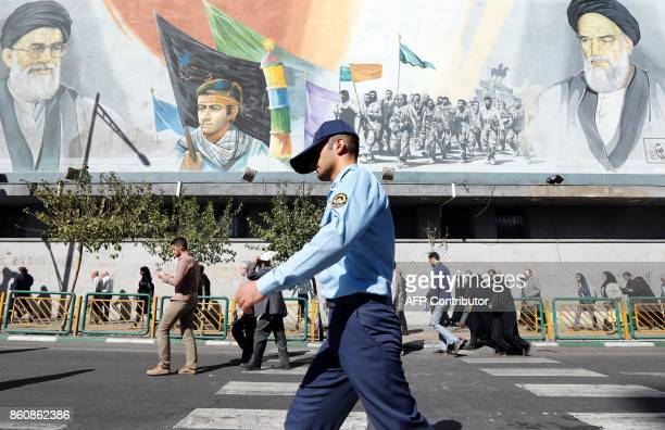 A member of the Iranian army walks past pictures of Iranian supreme leader Ayatollah Ali Khamenei and of late Iranian supreme leader Ayatollah...