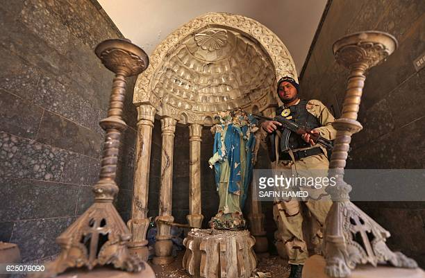 A member of the Iraqi Christian forces Kataeb Babylon wearing a bandana with an inscription saying Here I am O Mary stands guard carrying a...