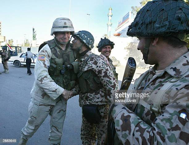 Member of the Iraqi Civil Defense Corps says goodbye to a US soldier after they conducted a joint patrol in central Baghdad 20 January 2004. In the...
