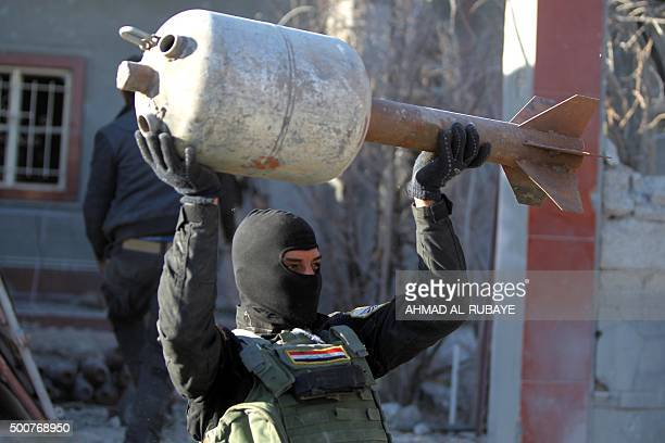 A member of the Iraqi counterterrorism forces carries a rocket locally made from domestic gas canisters from an arms depot that belonged to Islamic...