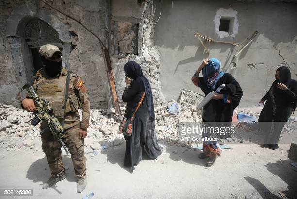 Member of the Iraqi Counter-Terrorism Forces stands guard as Iraqis flee the Old City of Mosul on July 3 during the ongoing offensive to retake the...