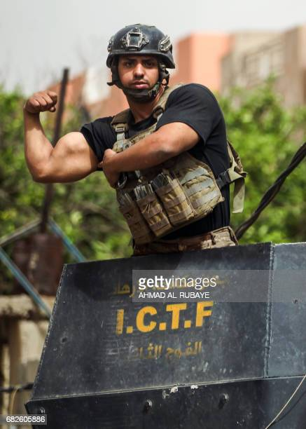 Member of the Iraqi Counter-Terrorism Service flexes his biceps from atop a turret while on patrol in western Mosul's al-Islah al-Zaraye...