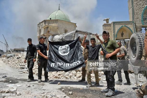 A member of the Iraqi CounterTerrorism Service raises the victory gesture as others hold upsidedown the black flag of the Islamic State group outside...