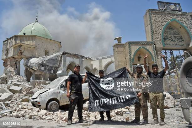 Member of the Iraqi Counter-Terrorism Service raises the victory gesture as others hold upside-down the black flag of the Islamic State group,...