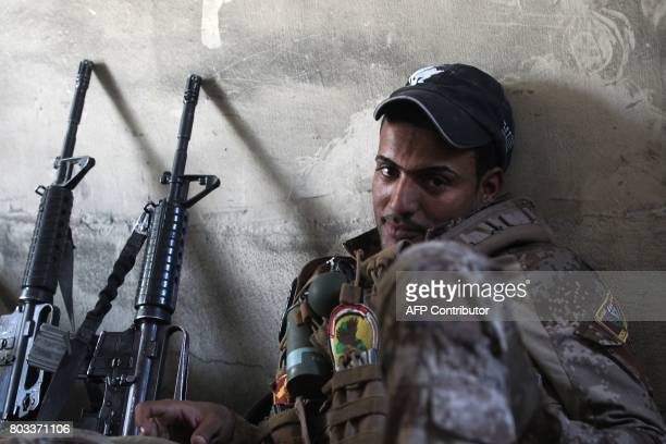 A member of the Iraqi CounterTerrorism Service rests during the advance towards the Grand Mosque of Nuri in the Old City of Mosul on June 29 as the...