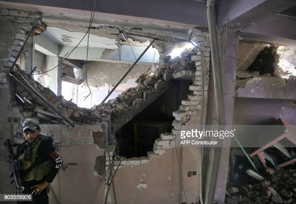 A member of the Iraqi CounterTerrorism Service stands in a damaged house during the advance towards the Grand Mosque of Nuri in the Old City of Mosul...