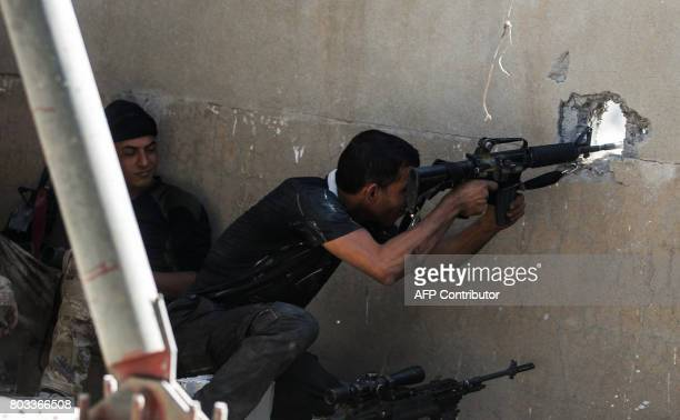 A member of the Iraqi CounterTerrorism Service takes aim behind cover during the advance towards the Grand Mosque of Nuri in the Old City of Mosul on...