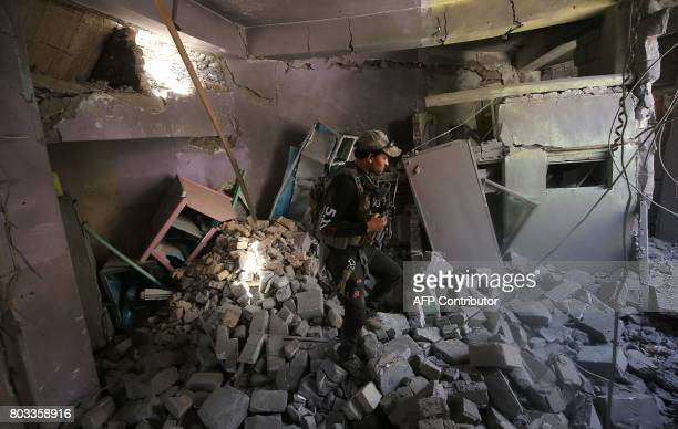 A member of the Iraqi CounterTerrorism Service walks through the rubble of a damaged house during the advance towards the Grand Mosque of Nuri in the...