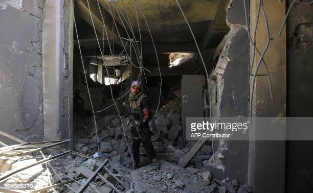 A member of the Iraqi CounterTerrorism Service walks through the rubble of a damaged building during the advance towards the Grand Mosque of Nuri in...