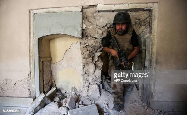 TOPSHOT A member of the Iraqi CounterTerrorism Service walks through the rubble and the broken wall of a damaged building during the advance towards...