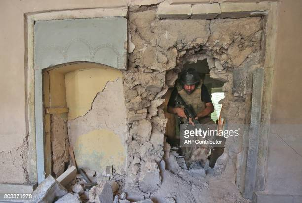 A member of the Iraqi CounterTerrorism Service walks through the rubble and the broken wall of a damaged building during the advance towards the...