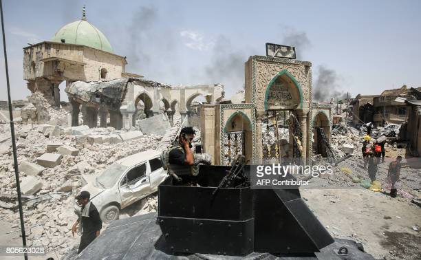 A member of the Iraqi CounterTerrorism Service wipes his face while standing in the turret of a humvee parked outside the destroyed gate of AlNuri...