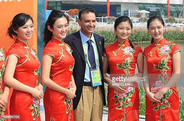 Member of the Iraqi delegation poses for pictures with Chinese Asian Games hostesses during the Iraqi flag raising ceremony at the 16th Asian Games...