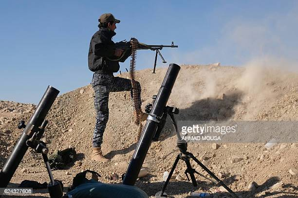 TOPSHOT A member of the Iraqi Federal Police fires his weapon at an Islamic State group target on the front line near the village of Tall AdhDhahab...