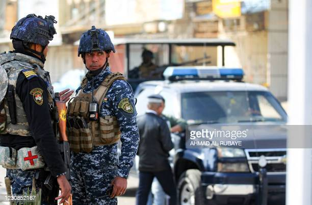 Member of the Iraqi federal police forces stand guard at a checkpoint in a street in the capital Baghdad on January 29 during tightened security...