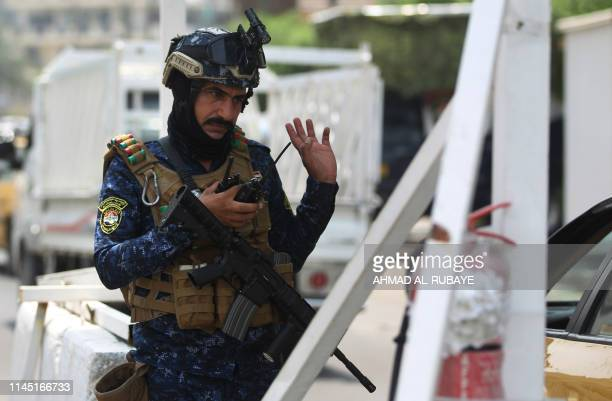 A member of the Iraqi federal police forces stands guard at a checkpoint in Baghdad's Karada district on May 20 2019 A Katyusha rocket crashed the...