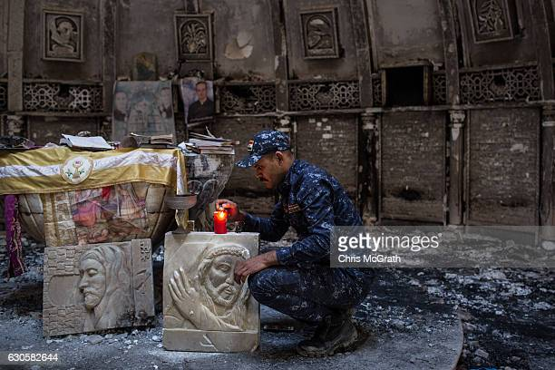 Member of the Iraqi federal police lights a candle inside a church burned and destroyed by ISIL during their occupation of the predominantly...