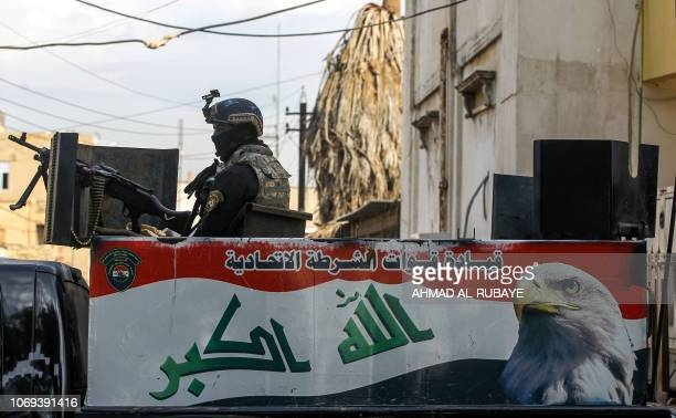 A member of the Iraqi federal police mans a turret while on guard as youths participate in the first children's marathon run in the capital Baghdad...