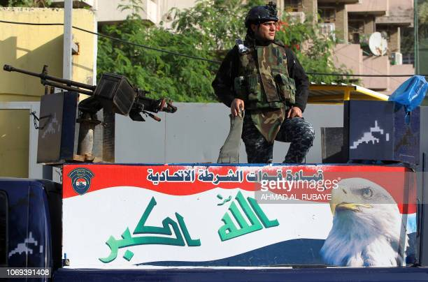 A member of the Iraqi federal police stands guard as youths participate in the first children's marathon run in the capital Baghdad on December 7 2018