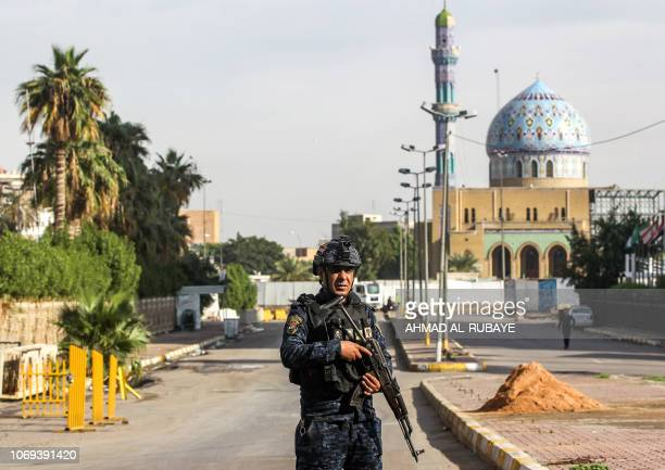 A member of the Iraqi federal police stands guard as youths participate in the first children's marathon run in the capital Baghdad on December 7...