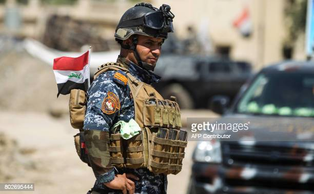 A member of the Iraqi federal police stands with an Iraqi flag stowed in the back of his ammunition pack during the advance through the Old City of...