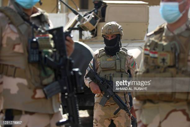 Member of the Iraqi force stands at attention during a search of the area in Tarmiyah, 35 kilometres north of Baghdad on February 20 following...