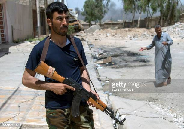 A member of the Iraqi forces carries a Kalashnikov assault rifle as he walks down a street before heading for combat in west Mosul on May 16 2017...
