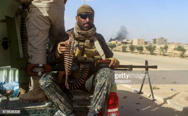 A member of the Iraqi forces carries a machine gun as he rides in the back of a pickup truck as they gather in the Rawa area during an operation to...
