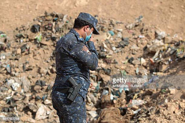 A member of the Iraqi forces checks a mass grave they discovered in the Hamam alAlil area on November 7 2016 after they recaptured the area from...