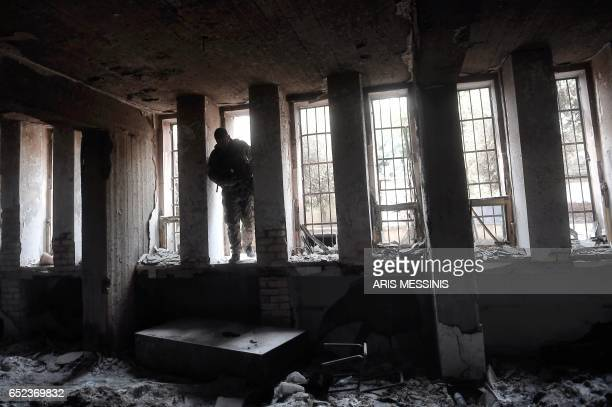 A member of the Iraqi forces enters the destroyed building of the museum of Mosul on March 11 2017 after it was recaptured from Islamic State group...