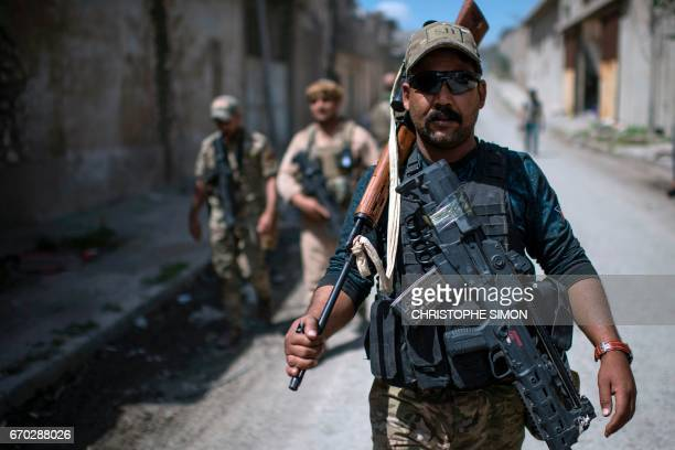 A member of the Iraqi forces from the elite Rapid Response Division walks down a street during their advance in western Mosul on April 19 as part of...