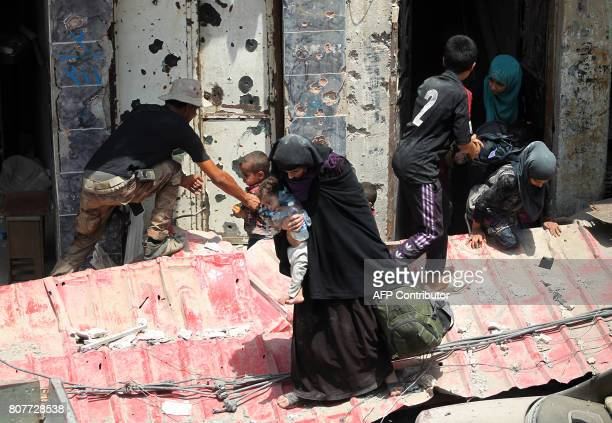 A member of the Iraqi forces help families flee their homes in Mosul's Old City on July 4 during the ongoing offensive to retake the city from...