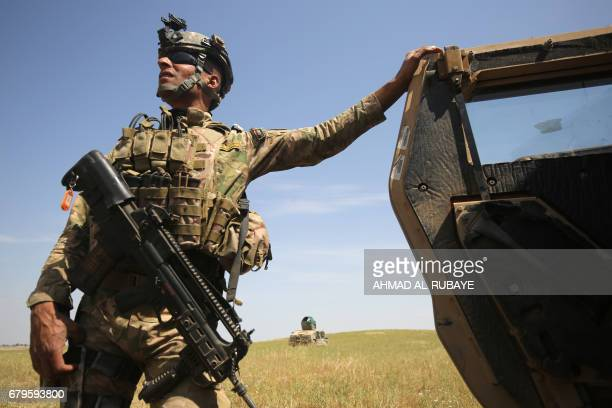 A member of the Iraqi forces leans up against a military vehicle as they advance towards the AlHaramat neighbourhood north of Mosul during the...