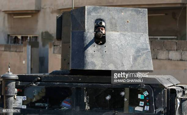 Member of the Iraqi forces mans a turret mounted atop a humvee as troops advance towards the Old City in western Mosul on March 24 during an...