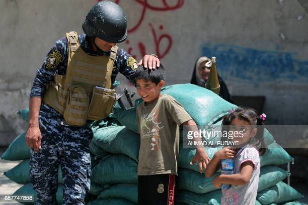 TOPSHOT A member of the Iraqi forces plays with children on the outskirts of the old city of Mosul on May 24 after the area was retaken by Iraqi...