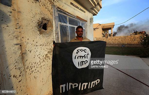 A member of the Iraqi forces poses for a photograph with an Islamic State group flag in front of a wall riddled with shrapnels in the village of...
