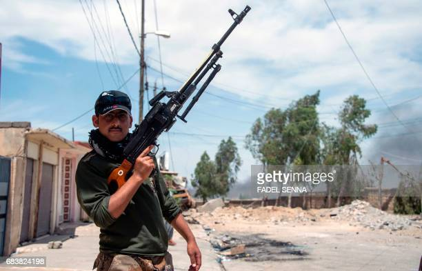 A member of the Iraqi forces poses for a picture carrying a PK machine gun before heading for combat in west Mosul on May 16 2017 during their...