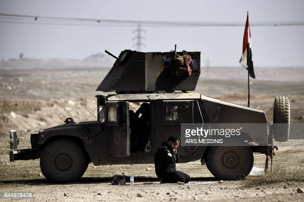TOPSHOT A member of the Iraqi forces pray next to an armoured vehicle as troops advance towards Mosul's on February 24 2017 during an ongoing...