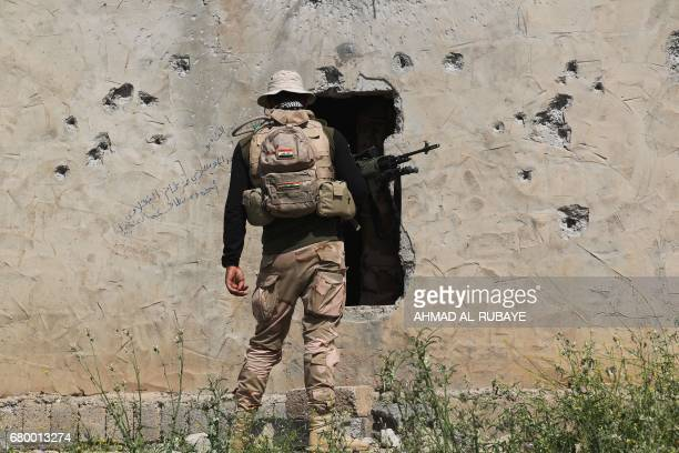 TOPSHOT A member of the Iraqi forces secures a building as troops advance towards the AlHaramat neighbourhood north of Mosul on May 7 during the...