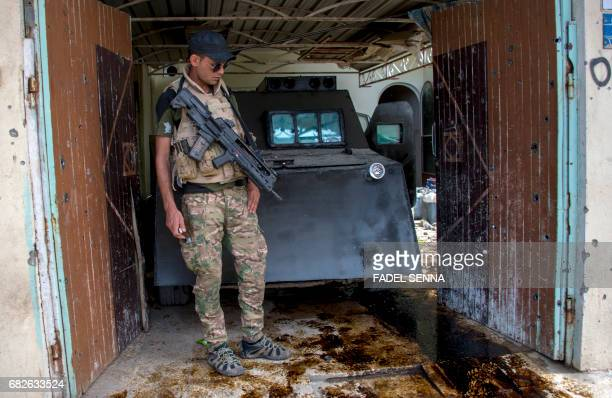 Member of the Iraqi forces stands next to a dismantled car bomb in Mosul's northwestern al-Haramat neighbourhood on May 13 during an ongoing...