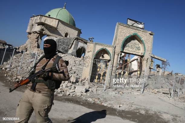 TOPSHOT A member of the Iraqi forces stands outside the destroyed AlNuri Mosque in Mosul's Old City on January 8 six months after troops seized the...