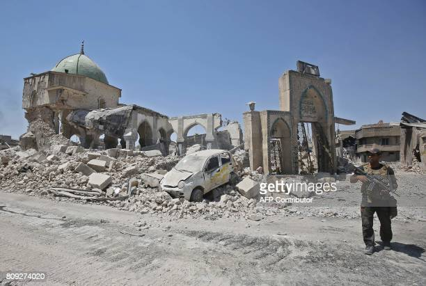 A member of the Iraqi forces stands outside the destroyed gate of the AlNuri Mosque in the Old City of Mosul on July 5 2017 during the Iraqi...